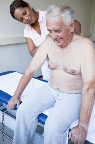 A massage therapist treating a senior man