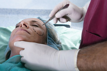 Surgeon with scalpel to patient's face