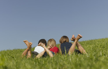 Three children lying in the grass together, view from behind