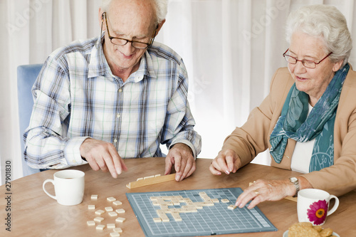 A senior couple playing a board game together