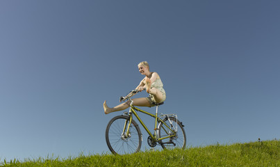 A woman freewheeling downhill on a bicycle in summertime