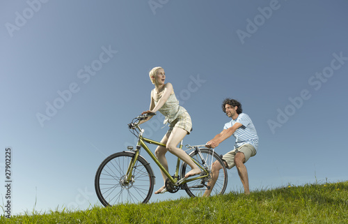 A woman on a bicycle, man holding onto the back