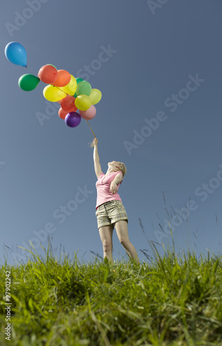 A woman holding a bunch of colorful balloons in summertime
