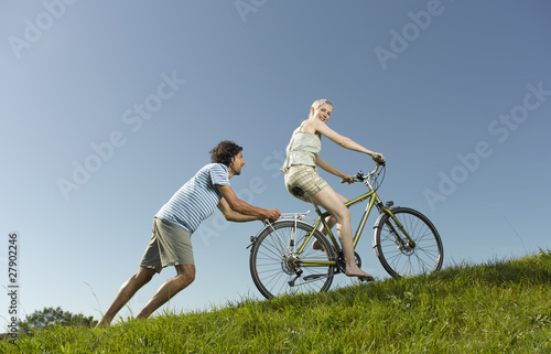 A woman on a bicycle, man pushing her uphill