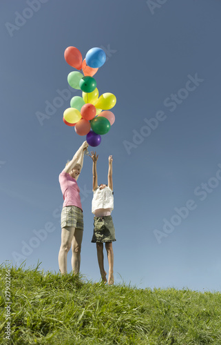 Mother holding a bunch of colorful balloons, daughter reaching to get them