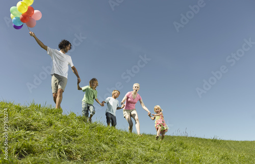 A family walking through the grass holding hands, father holding a bunch of colorful balloons