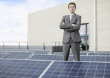 A businessman standing amongst solar panels
