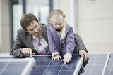 A businessman showing a solar panel to a young girl