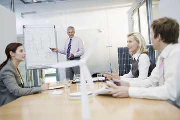 Four businesspeople discussing an alternative energy project
