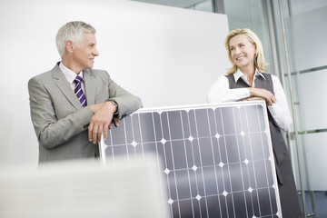 A businessman leaning on a solar panel talking to a female colleague