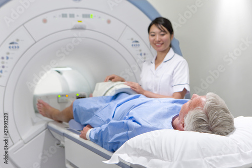 Radiologist helping patient with MRI scanning machine