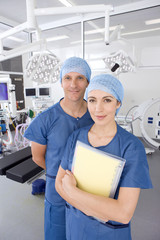 Surgeons standing with medical chart in hospital operating room