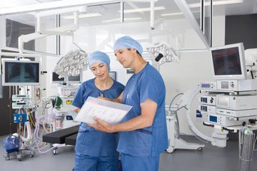 Surgeons reviewing medical chart in hospital operating room