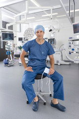 Surgeon sitting on stool in hospital operating room