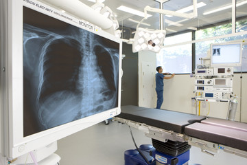 Surgeon standing in hospital operating room with x-ray and equipment