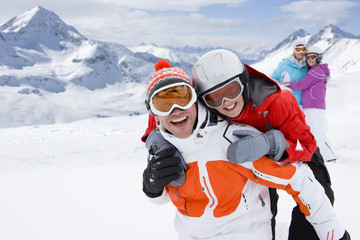 Family playing in snow with mountain in background