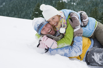 Playful couple laying and hugging in snow