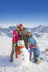 Family building snowman together