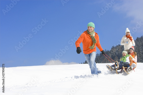 Father pulling children on sled downhill on ski slope