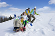 Parents on ski slope pulling children up hill on sled
