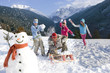 Family having snowball fight on ski slope near snowman