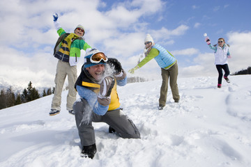Family having snowball fight on ski slope