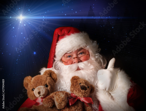 Santa smiling holding toy teddy bears
