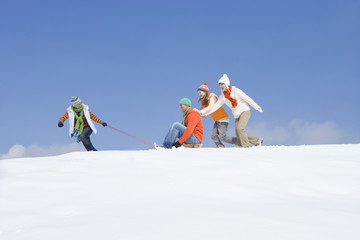 Family playing with sled on ski slope