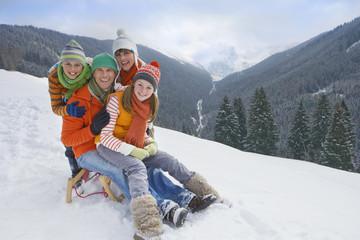 Smiling family sitting on sled on ski slope