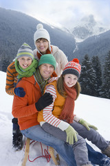 Smiling family sitting on sled on ski slope