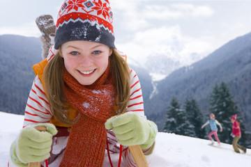 Close up of girl laying on sled on ski slope