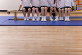 School children sitting on bench in school gymnasium