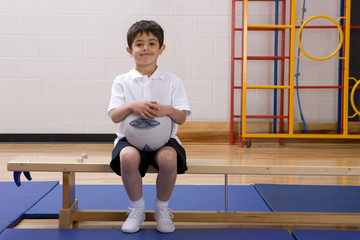 School boy sitting on bench and holding ball in school gymnasium