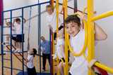School children climbing gymnasium climbing equipment
