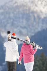 Couple holding hands, carrying skis and looking at mountain