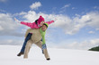 Man giving girlfriend piggyback ride through snow