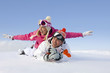 Woman with outstretched arms laying with boyfriend in snow