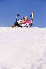 Couple sitting in snow with skis
