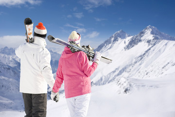 Couple holding hands, carrying skis and looking at mountains