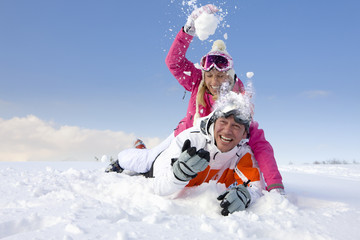 Couple laying in snow and having snowball fight