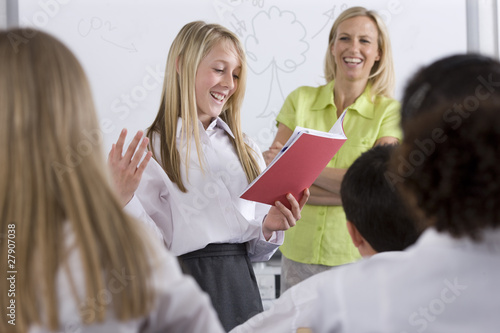 School girl reading out of test booklet in classroom to classmates