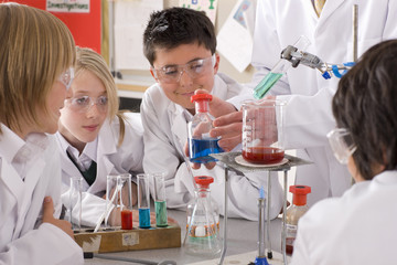 Students watching chemistry teacher conduct experiment in laboratory