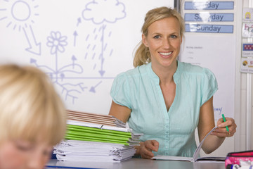 School teacher grading notebooks in classroom