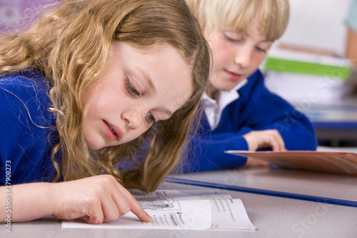 School girl reading workbook in classroom