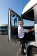 Truck driver climbing into cab of semi-truck