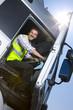 Truck driver closing door of semi-truck