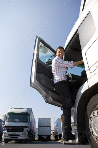 Truck driver climbing in to cab of semi-truck