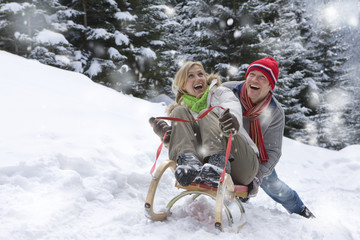 Man pushing girlfriend on sled on remote snowy hillside