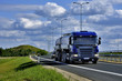 Blue heavy truck with container on the road at the sunny day.