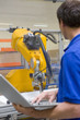 Worker watching robotic arm working on assembly line in factory